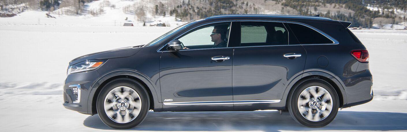 side view of blue 2019 kia sorento driving on snowy road