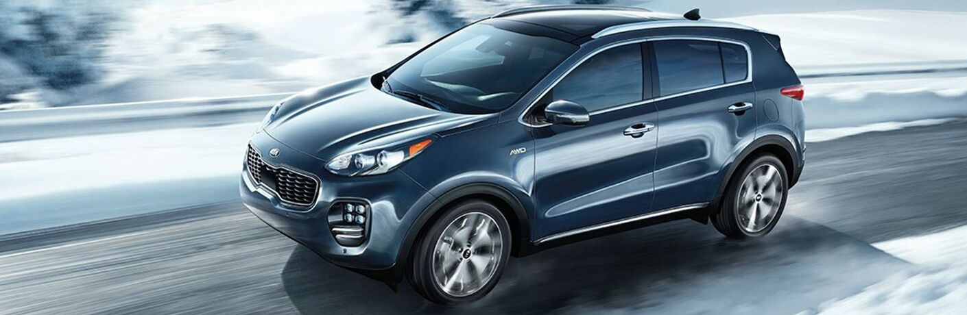 blue 2019 kia sportage driving on snowy road