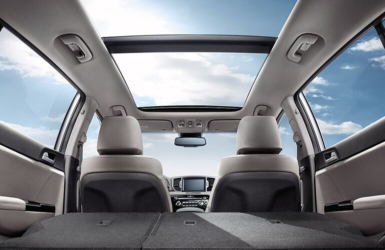 interior of 2019 kia sportage with rear seats folded down looking up through panaoramic moonroof