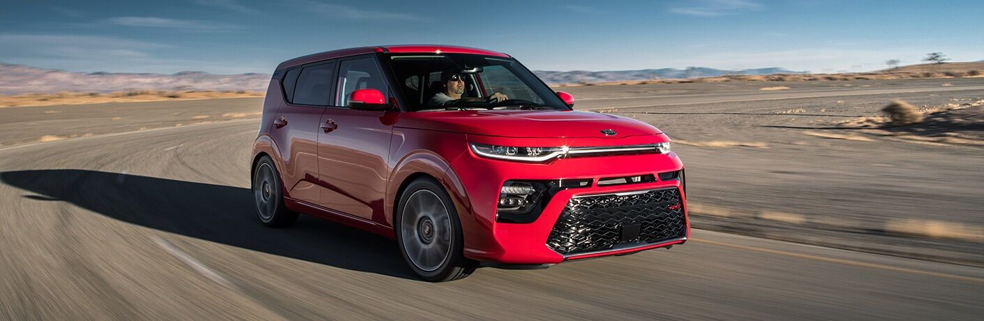 Man driving behind the wheel of a red 2020 Kia Soul