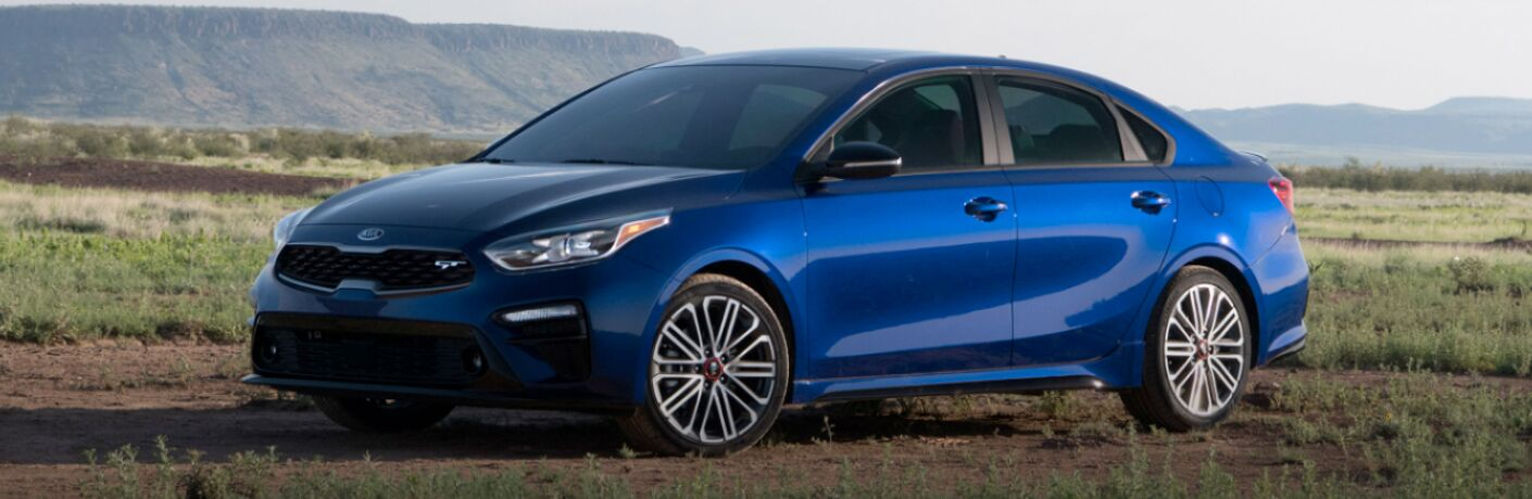 2020 Kia Forte blue exterior driver side front parked in field large rock formations in background