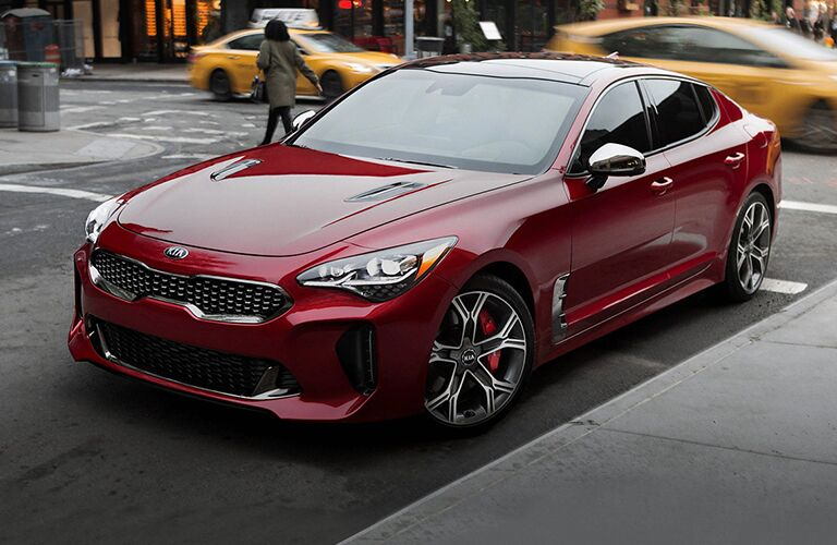 2020 Kia Stinger red exterior front driver side driving in busy city