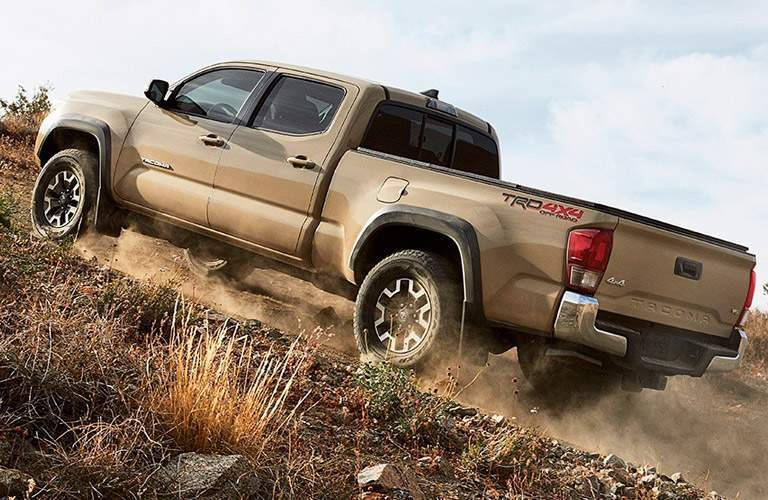 Tan Toyota Tacoma scaling up hill
