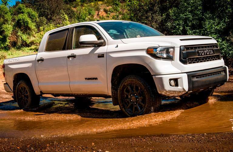 White Toyota Tundra driving through mud