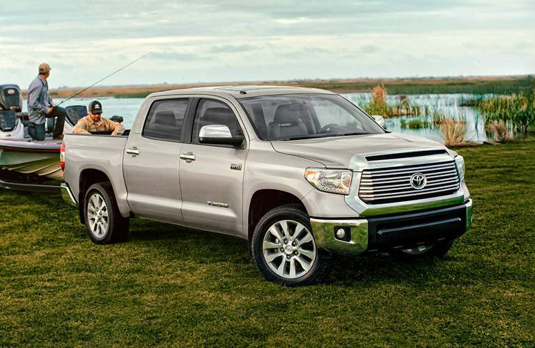 Fishermen attaching boat to rear of 2018 Toyota Tacoma