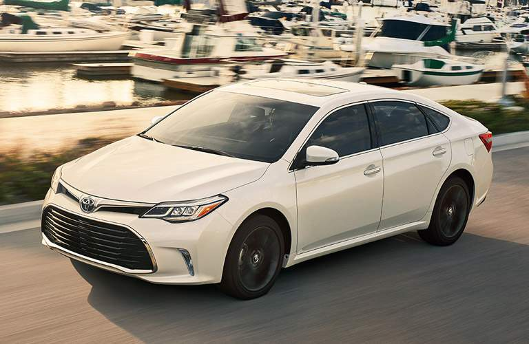 White Toyota Avalon driving on road with boats in background