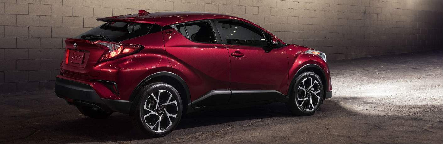 Red Toyota C-HR parked in dark alleyway next to brick wall