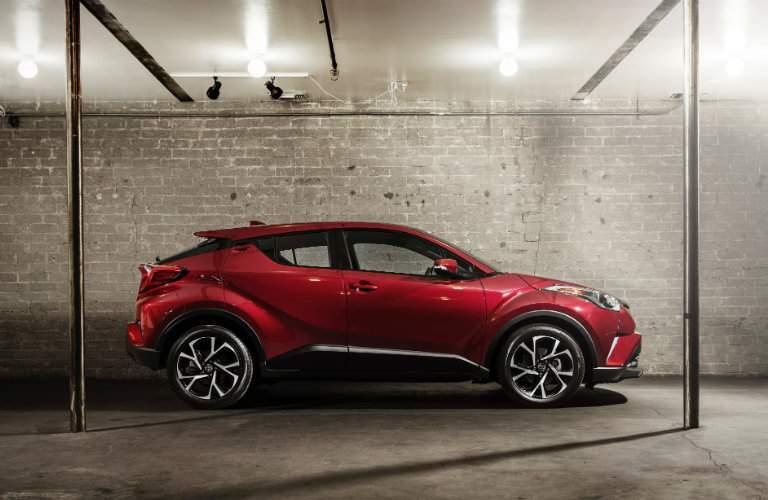 Red 2018 Toyota C-HR parked in between two poles in garage