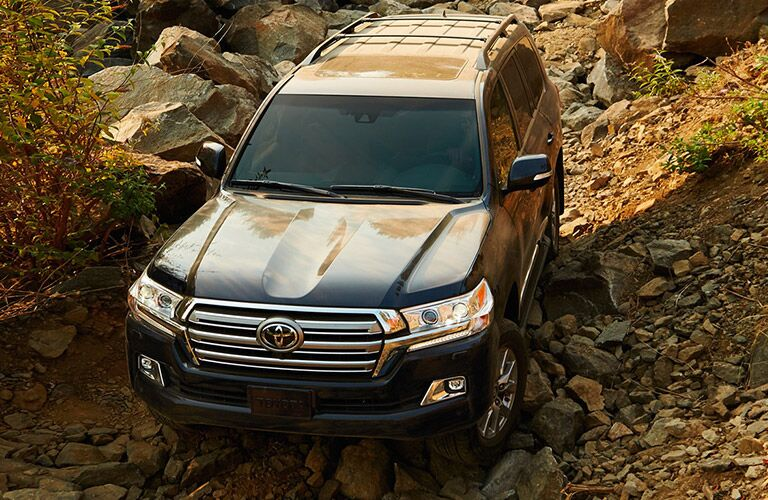 Blue Toyota Land Cruiser driving on rock formation