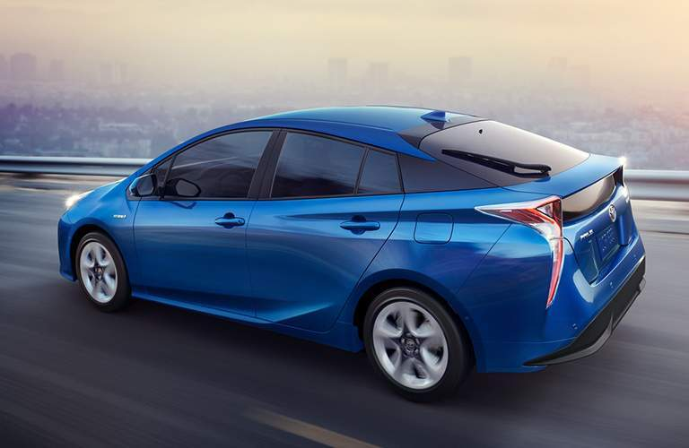 Rear shot of blue 2018 Toyota Prius driving with city skyline in background