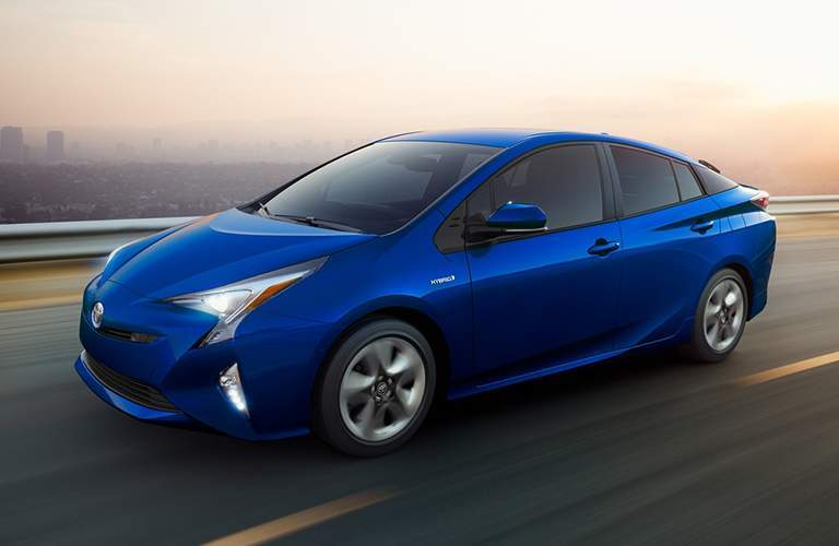 Blue Toyota Prius driving with city skyline in background