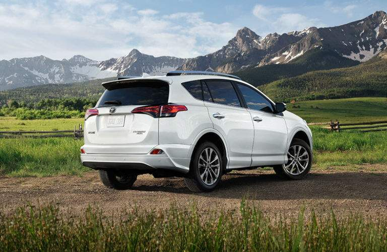 Rear shot of white 2018 Toyota RAV4 parked in field with mountains in background