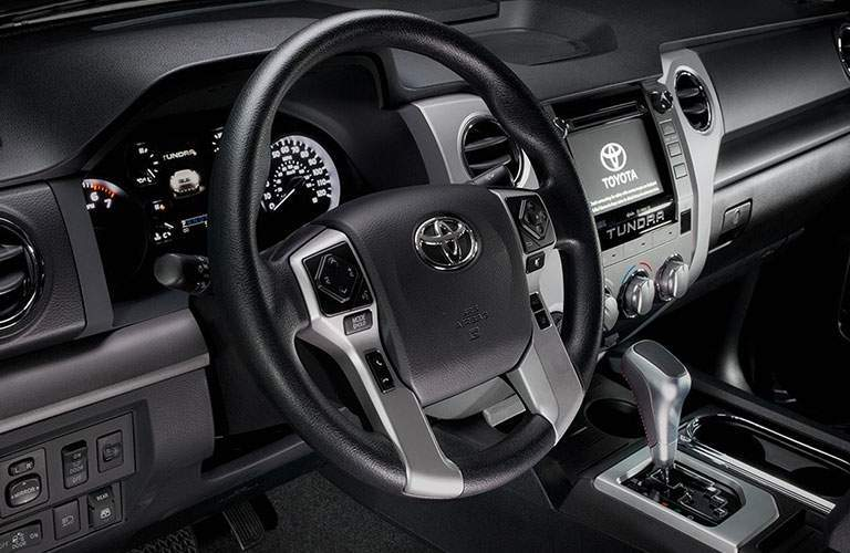 Interior shot of 2018 Toyota Tundra with steering wheel shown alongside touchscreen interface and information display