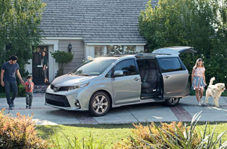 Family and dog walking around silver Toyota Sienna