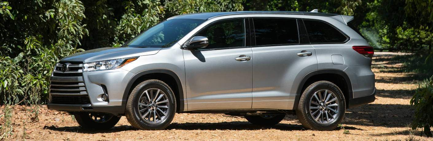 Profile shot of silver 2018 Toyota Highlander parked on dirt road in daytime