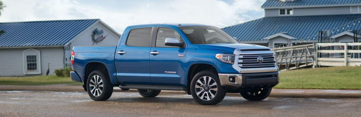 Blue 2018 Toyota Tundra model parked in front of two blue roofed houses