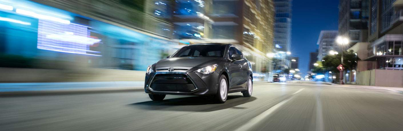 Gray 2018 Toyota Yaris iA driving down city street at night with lights illuminating path