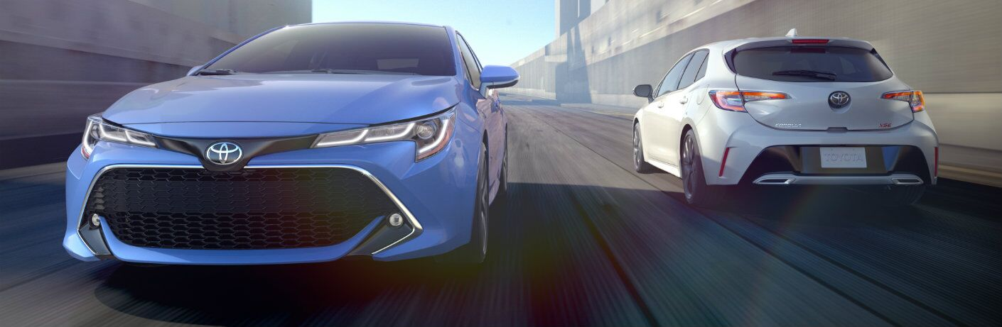 Two 2019 Toyota Corolla hatchback models driving in opposite direction down road
