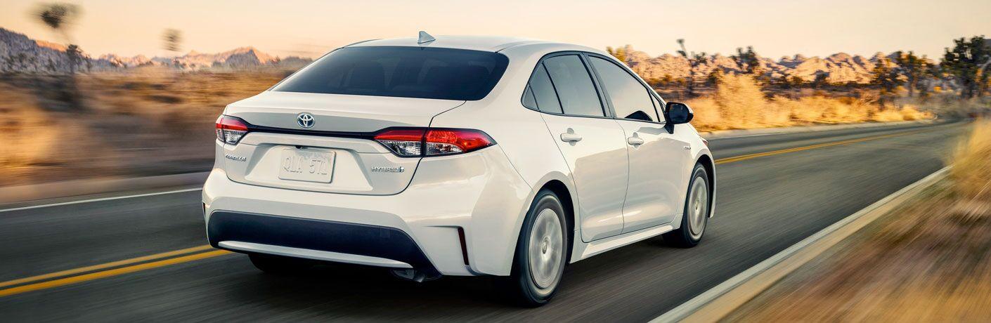 white 2020 Toyota Corolla Hybrid driving down desert road