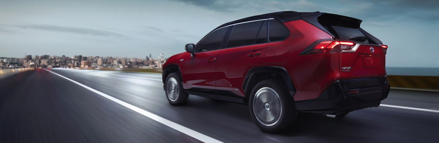 red 2021 Toyota RAV4 Prime driving into a city