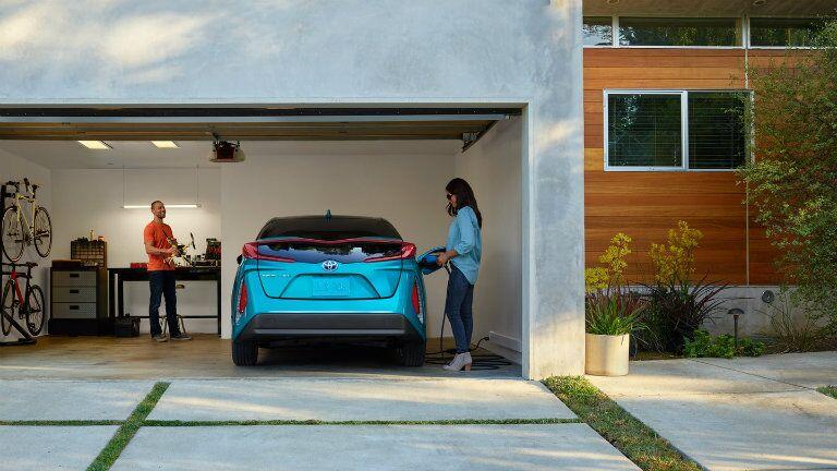 Blue Prius Prime charging in garage