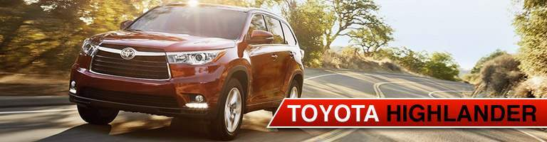Red Toyota Highlander SUV driving down forested road