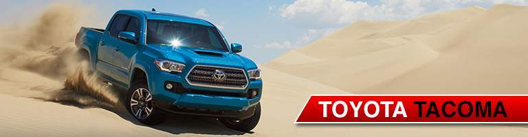 Blue Toyota Tacoma driving down sand dune while kicking up sand behind
