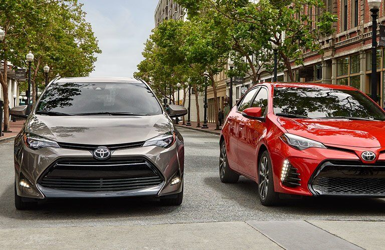a red and beige 2017 Toyota Corolla driving through the streets