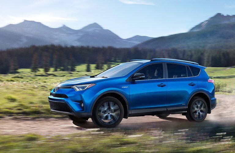 side view of a blue 2017 Toyota RAV4 with a mountain background