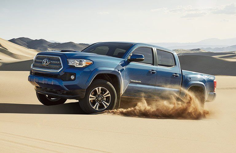 side view of a blue 2017 Toyota Tacoma driving among sand dunes
