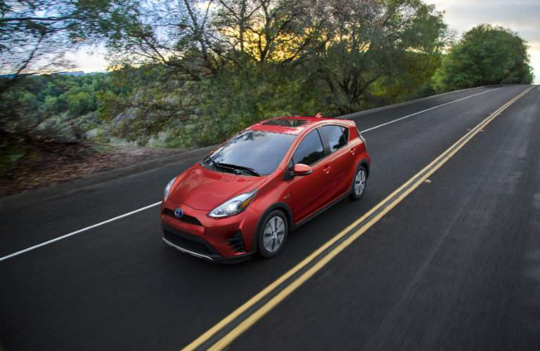 red 2018 Toyota PriusC driving through the country