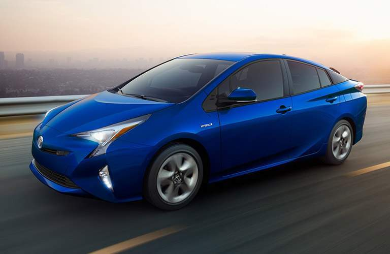 side view of a blue 2018 Toyota Prius, driving past a blurred background