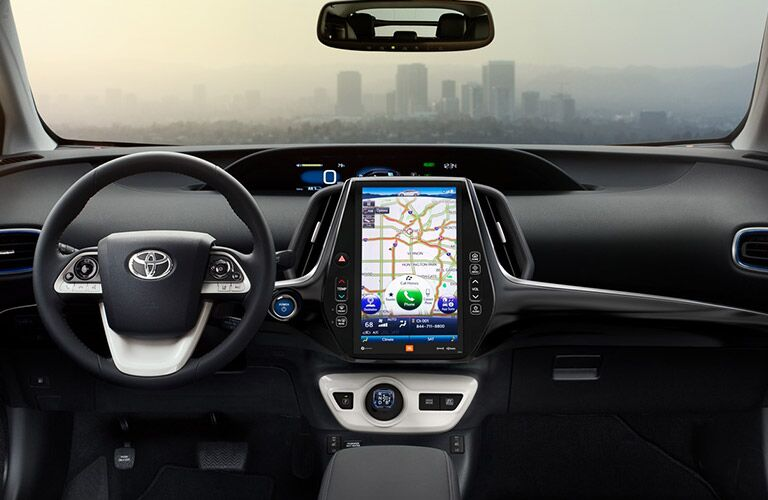 steering wheel and dashboard in 2018 Toyota Prius with city skyline through windshield