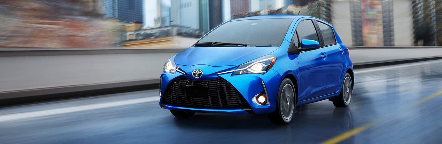 blue 2018 Toyota Yaris driving on a highway through a city