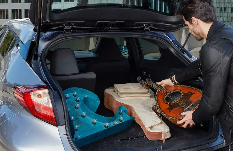 man putting instrument, possibly a mandolin, into the rear of the 2018 Toyota C-HR