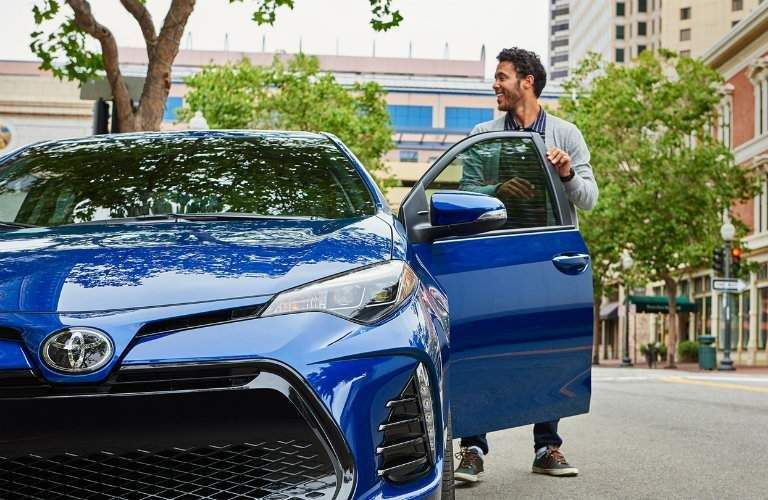 front view of a smiling man getting into the 2018 Toyota Corolla