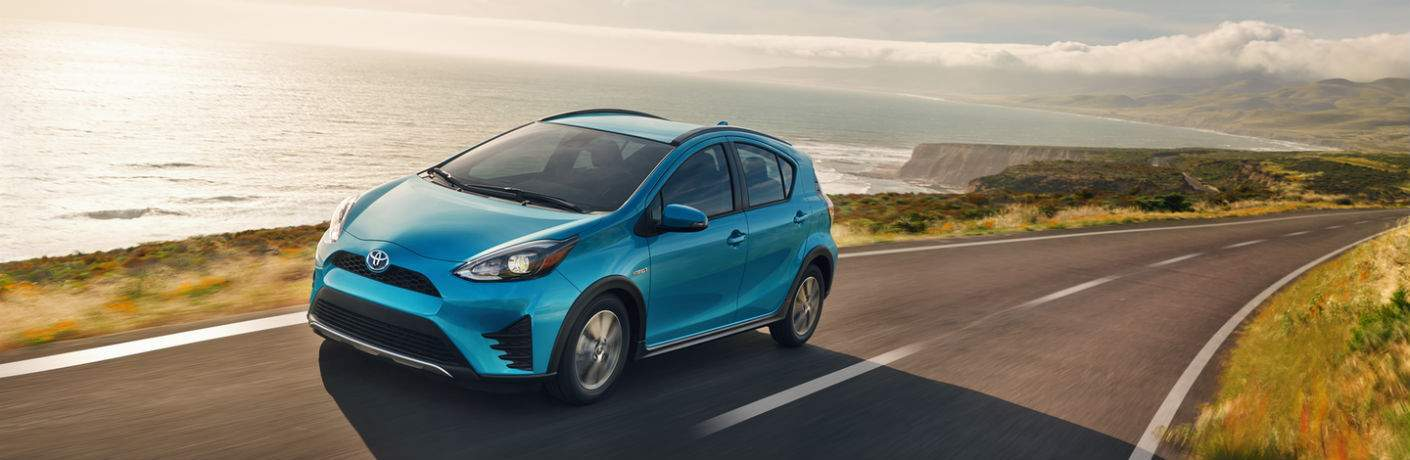 blue 2018 Toyota Prius c driving along a lake