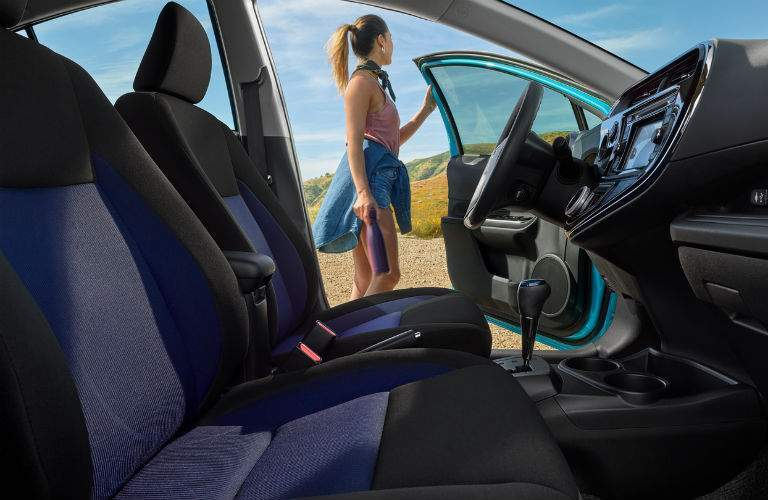 2018 Toyota Prius c black and blue front seats with a woman in the background