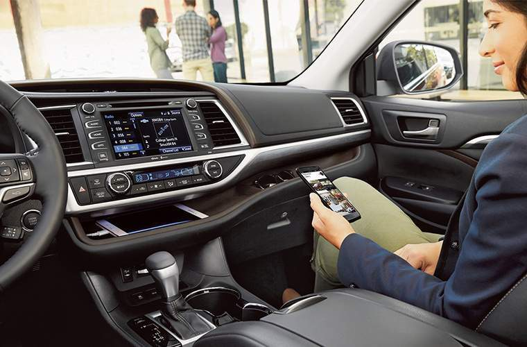 woman looking at her phone in the passenger seat of the 2018 Toyota Highlander with the infotainment system and tablet storage