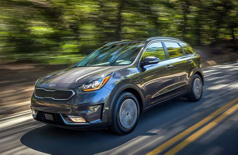 Gray 2018 Kia Niro driving down wooded road