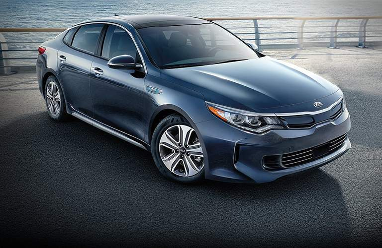 Blue 2018 Kia Optima parked on driveway with waterfront in view