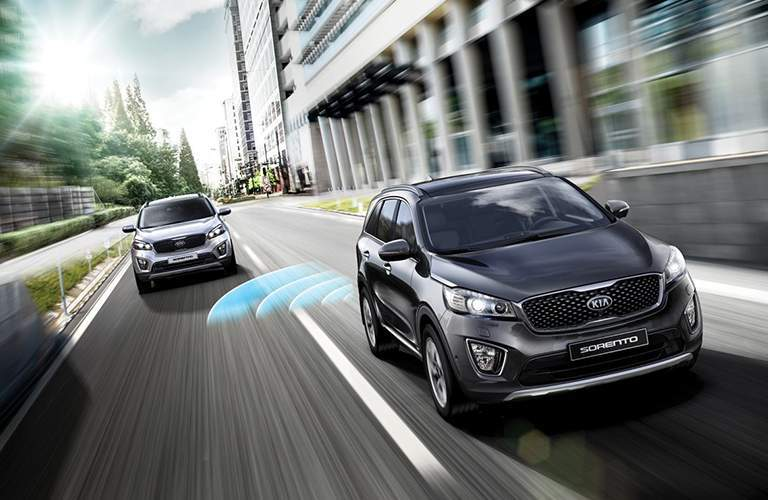 2018 Kia Sorento driving on highway road with driver assistance features illustrated