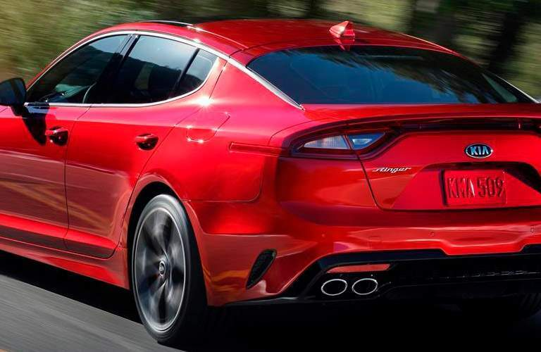 Rear view of red 2018 Kia Stinger driving on wooded road in daytime