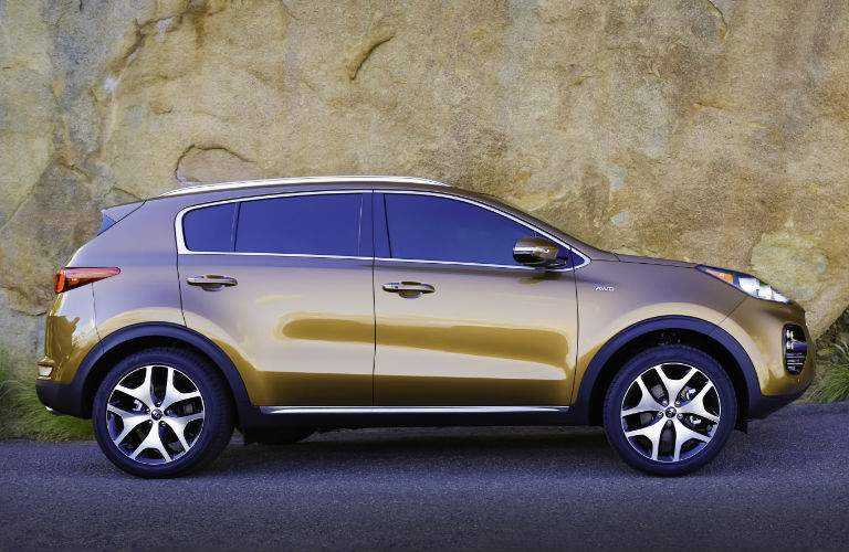 Profile view of brown 2018 Kia Sportage parked in front of rock formation
