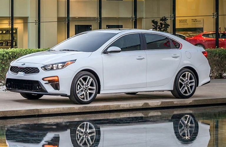 Exterior view of a white 2019 Kia Forte parked outside a Kia dealership
