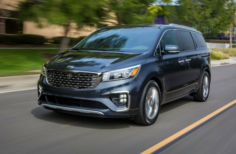 Exterior view of the front of a blue 2019 Kia Sedona driving down a suburban street