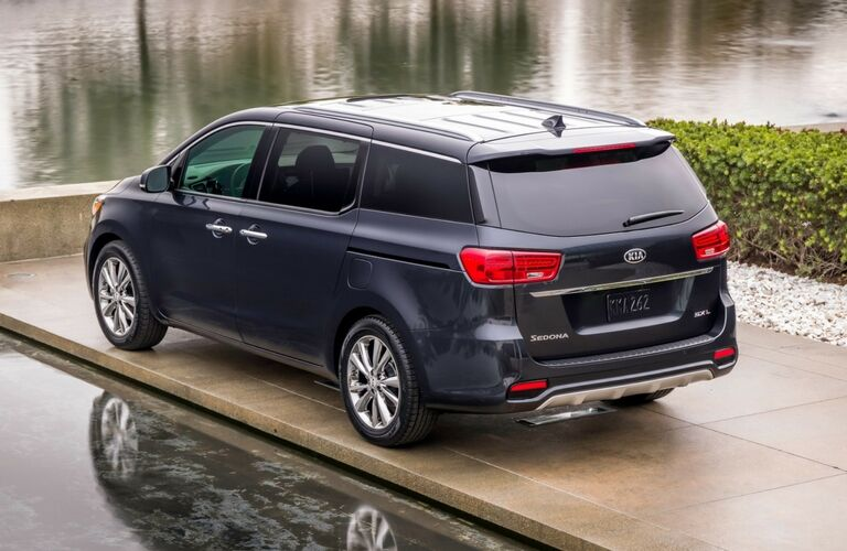 Exterior view of the rear of a blue 2019 Kia Sedona parked near a body of water