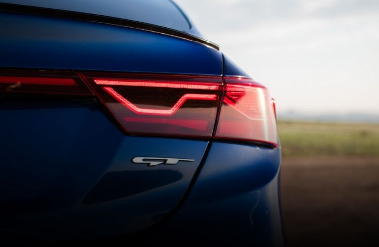 Exterior closeup view of the taillights and GT badge on a blue 2020 Kia Forte