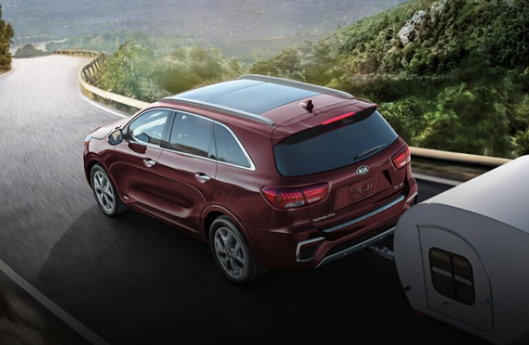 2020 Kia Sorento towing trailer on mountain road toward city