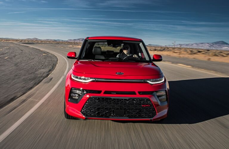 Exterior view of the front of a red 2020 Kia Soul driving down a desert highway
